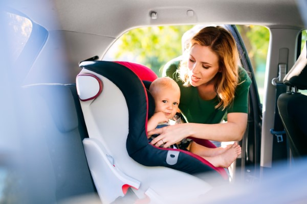 Young mother putting baby in the car seat.